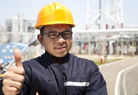 chemical industrial engineer with thumbs up and large oil refinery background photo