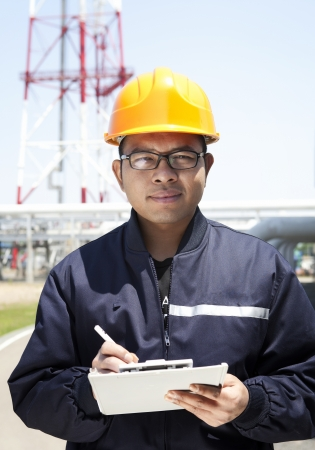 Chemical industrial engineer holding a notepad  with oil refinery background