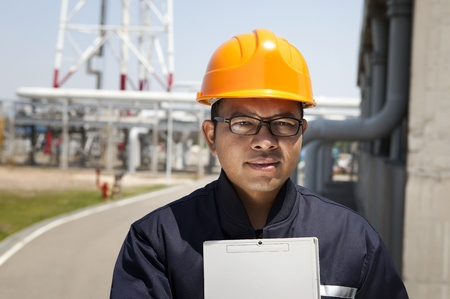 Chemical industrial engineer holding a notepad  with oil refinery background photo