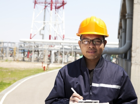 trabajador petrolero: Retrato de Asia ingeniero de pie delante de la gran fábrica
