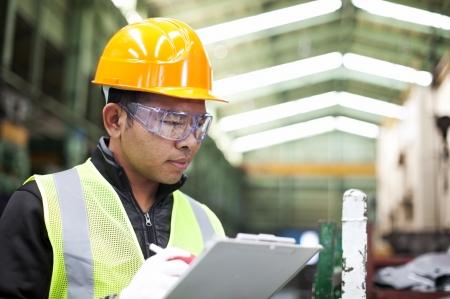 safety check: F�brica de escritura en el sujetapapeles trabajador estaba revisando el trabajo Foto de archivo
