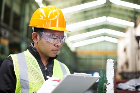 Factory worker writing on clipboard was checking work photo
