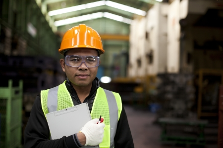 Portrait of asian engineer holding a notepad in the factory photo