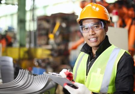Portrait d'un jeune ingénieur en prenant des notes