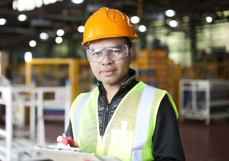 Portrait of asian engineer taking notes in the factory photo