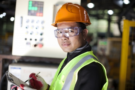 Portrait of asian engineer taking notes in the factory