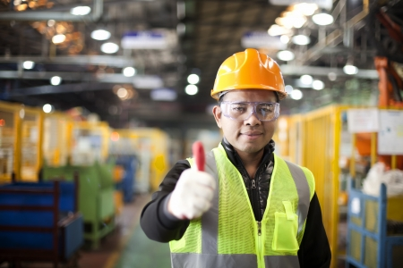 Portrait asian engineer showing thumb up in factory photo