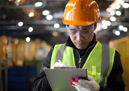 operante: scrittura ingegnere industriale sul blocco note in fabbrica
