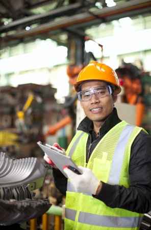 automotive industry: industrial engineer taking notes in factory vertical image