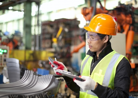 process industry: worker in factory checking quality of metals