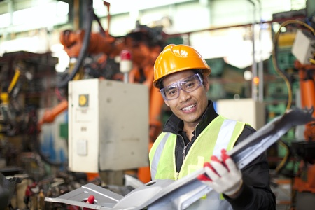 inspecting: industrial engineer checking quality of metal in factory Stock Photo