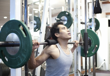 asian man gym workout, using a squat machine at fitness club photo