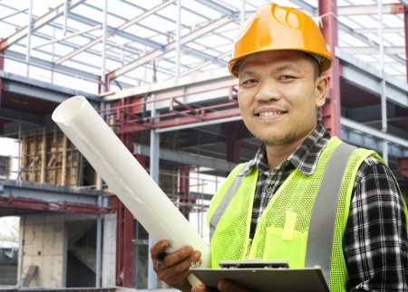 Male construction worker wearing safety vest at a building site Standard-Bild