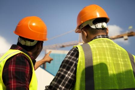 Deux travailleurs de la construction portant le gilet de sécurité recherche et pointant grue jaune au chantier de construction