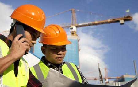 Bauarbeiter Blick auf Blueprint auf Baustelle und einem Menschen sprechen über das Telefon Standard-Bild - 21963016