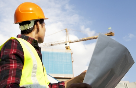 Engineer builder with blueprint at construction site Stock Photo