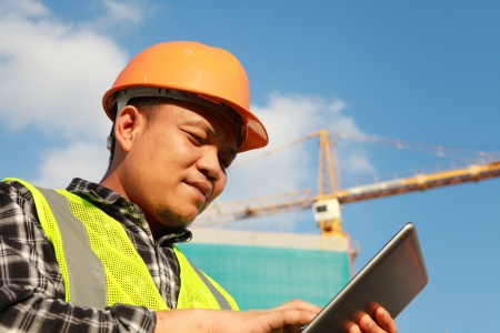 construction worker using digital tablet with crane on the background Imagens