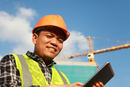 buliding: construction worker with digital tablet looking at you camera