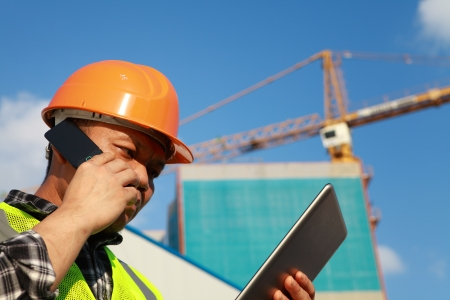 Construction worker activity with mobile phone and digital tablet
