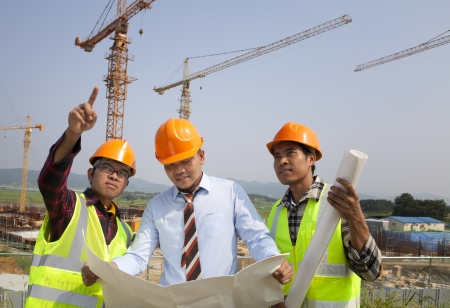 Architect and construction workers discussion on site with yellow cranes on the background