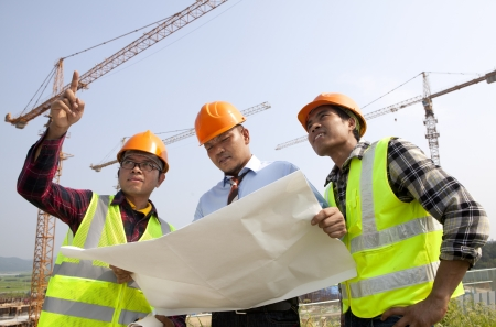 Group architect wearing a safety vest standing in front of a building site and a discussion photo