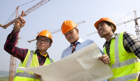 Group asian architect wearing a safety vest standing in front of a building site and a discussion photo