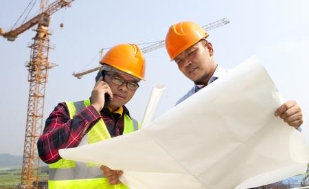 Construction builder looking at plans, conversation via mobile phone Standard-Bild