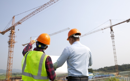 site: Site manager and construction worker checking plans on location Stock Photo
