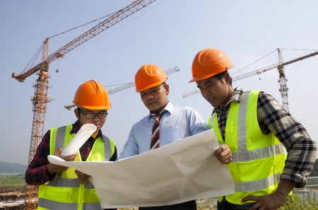 Architects at a construction site looking at blueprint discussion under cranes
