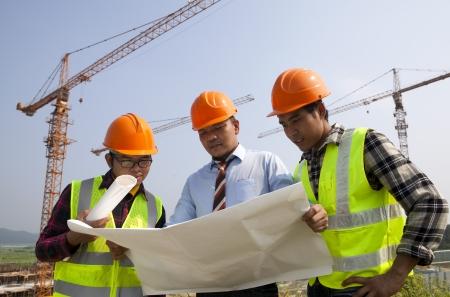 ingeniero civil: Arquitectos en un sitio de construcción mirando discusión plan bajo grúas Foto de archivo