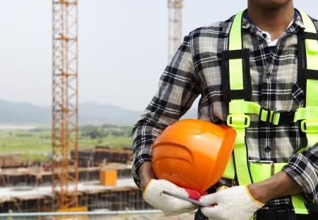 建設安全コンセプトのヘルメットを保持しているクローズ アップの建設労働者 写真素材