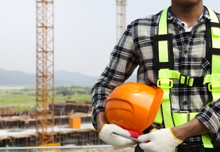 Close-up construction worker holding helmet, construction safety concept