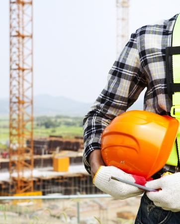 垂直方向の画像建設安全コンセプト、クローズ アップ建設作業員のヘルメットを保持