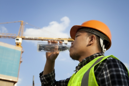 Tired construction worker drinking water with crane on the background