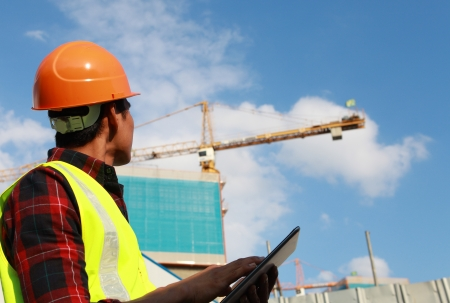 job site: builder worker activity with digital tablet on construction site Stock Photo