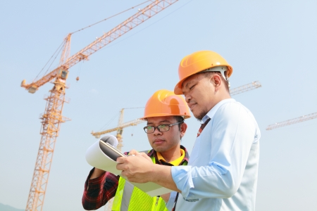 construction worker and manager checking a notepad on building new site photo