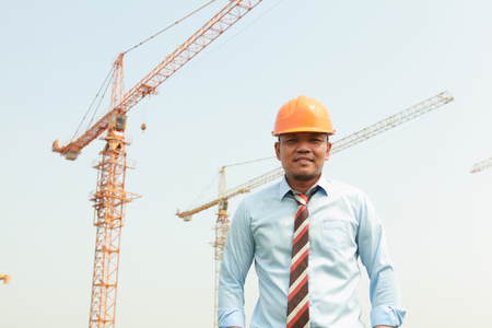 Manager standing on construction site with cranes on the background photo