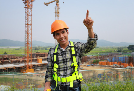 Construction worker at a building site pointing at something  photo