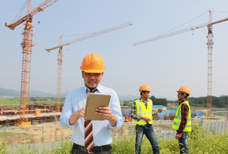 manager using digital tablet with worker on the background photo