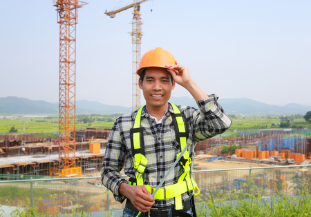 Builder worker with safety belt standing on construction site and cranes on the background