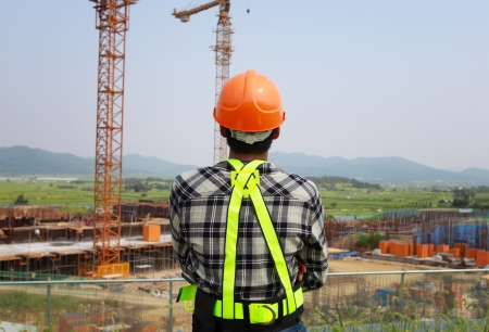 Builder inspector checking a construction site works.  Imagens