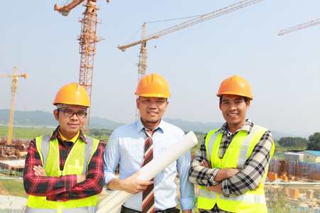 Group of workers and manager standing under crane photo