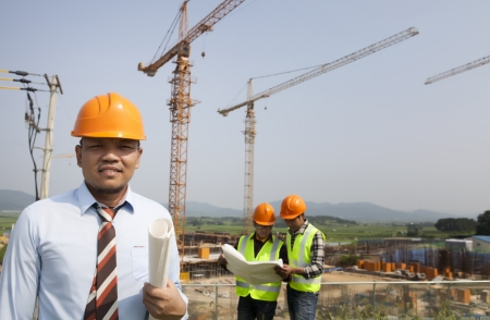 asian architect: manager surveying on construction site