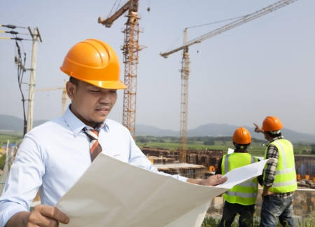 construction management project: Construction manager checking plans  building project on site