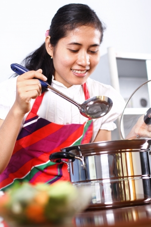 food testing: Asian woman tasting her cooking