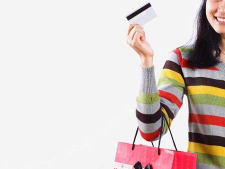 Girl with shopping bag and credit card isolated on white background photo