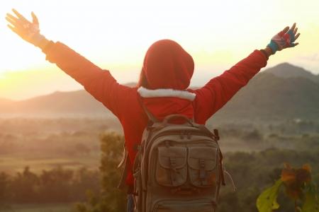 Femme heureuse propagation mains debout regarder le lever du soleil. Randonnée en montagne Banque d'images