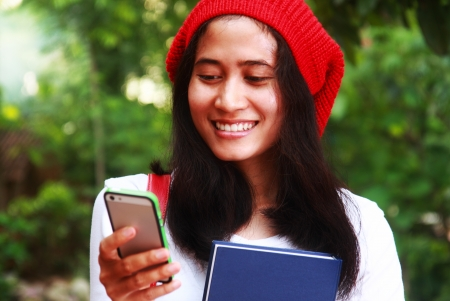 Female student typing message on the phone, holding her book standing in the park photo