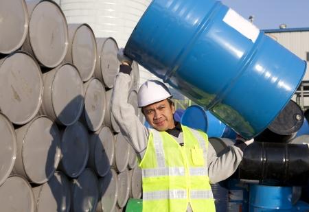 worker lifting drum on warehouse Standard-Bild