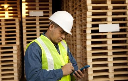 Arbeitnehmer mit Smartphone in der Palettenlager Standard-Bild - 24643774